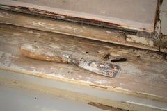 Винтажное восстановление окна, нож замазки и старая, который извлекли краска от древесины стоковое фото