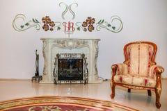 Винтажное кресло около камина Стоковые Изображения
