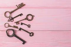 Винтажное собрание ключей на розовой предпосылке влюбленность и сновидение скопируйте космос стоковая фотография