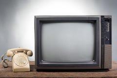 Винтажное телевидение с старым телефоном на деревянной таблице Стоковое Изображение RF