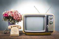 Винтажное телевидение с старым телефоном на деревянной таблице Стоковая Фотография