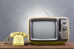 Винтажное телевидение с старым телефоном на деревянной таблице Стоковые Изображения RF