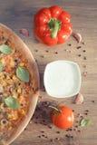 Винтажное фото, вегетарианская пицца и ингридиенты с специями на деревенской деревянной предпосылке Стоковые Изображения