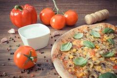 Винтажное фото, вегетарианская пицца и ингридиенты с специями на деревенской деревянной предпосылке Стоковое Изображение