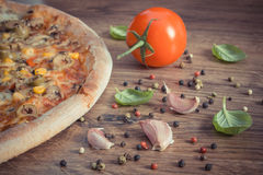 Винтажное фото, вегетарианская пицца и ингридиенты с специями на деревенской деревянной предпосылке Стоковые Фото