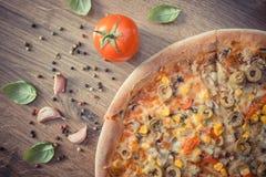 Винтажное фото, вегетарианская пицца и ингридиенты с специями на деревенской деревянной предпосылке Стоковая Фотография
