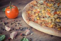 Винтажное фото, вегетарианская пицца и ингридиенты с специями на деревенской деревянной предпосылке Стоковая Фотография RF