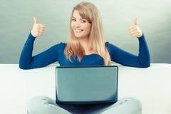 Винтажное фото, женщина при компьтер-книжка сидя на софе и показывая большие пальцы руки вверх Стоковая Фотография