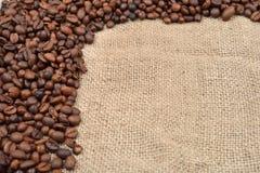 Винтажное фото, зажаренные в духовке кофейные зерна на коричневой предпосылке джута Mo Стоковое Изображение