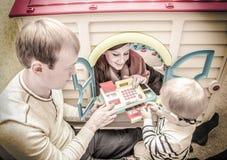 Винтажное фото молодой семьи играя с кассовым аппаратом игрушки внутри Стоковое Изображение RF