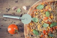 Винтажное фото, резец пиццы с вегетарианской пиццей, ингридиентами с специями на деревянной предпосылке Стоковые Изображения RF