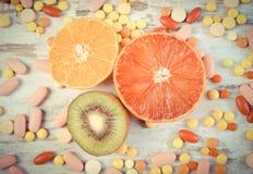 Винтажное фото, свежие фрукты и красочные медицинские пилюльки, выбор между здоровым питанием и медицинскими дополнениями Стоковое Фото