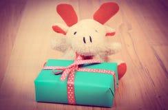 Винтажное фото, северный олень плюша с подарком для рождества или другое торжество Стоковая Фотография