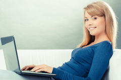 Винтажное фото, счастливая женщина при компьтер-книжка сидя на софе, современной технологии Стоковые Изображения RF