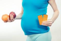 Винтажное фото, удерживание беременной женщины плодоовощи и медицинские пилюльки или дополнения, выбор между здоровой едой и пилю Стоковые Фотографии RF
