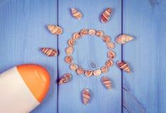 Винтажное фото, Seashells в форме солнца и лосьона солнца на досках, аксессуарах на лето Стоковые Фото