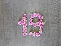 19, 19 - винтажное число розовых роз на предпосылке темной древесины стоковая фотография rf