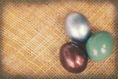 Винтажные бумажные текстуры, красочные пасхальные яйца на бамбуковом weave Стоковая Фотография