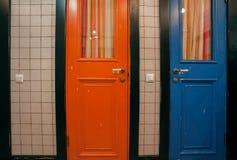 Винтажные деревянные двери старой ванной комнаты дома Голубые и красные дверь и зеркало над washbasin Стоковая Фотография RF