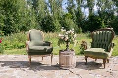 Винтажные деревянные стулья и таблица с украшением цветка в саде напольно Стоковое Изображение