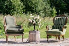 Винтажные деревянные стулья и таблица с украшением цветка в саде напольно Стоковые Фото
