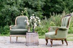 Винтажные деревянные стулья и таблица с украшением цветка в саде напольно Стоковые Фотографии RF