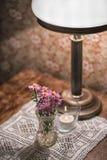 Винтажные детали вазы с цветками на деревянном столе и лампе Стоковая Фотография