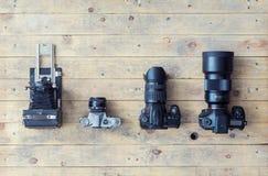 Винтажные и современные камеры на деревянной предпосылке Стоковые Фотографии RF