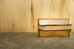Винтажные книги на каменной таблице против деревянной предпосылки Стоковые Изображения