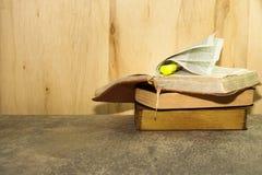 Винтажные книги на каменной таблице против деревянной предпосылки Стоковая Фотография