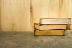 Винтажные книги на каменной таблице против деревянной предпосылки Стоковые Фотографии RF