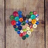 Винтажные кнопки в форме сердца на деревянной предпосылке Стоковая Фотография RF