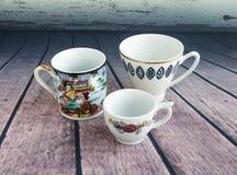 Винтажные кофейные чашки на деревянной предпосылке 3 малых чашки Стоковые Фотографии RF