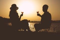 Винтажные пары, люди и женщины с стеклами вина в его руке на речном береге в лете на природе Стоковая Фотография