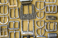 Винтажные пряжки пояса помещенные на желтой ткани Стоковое Фото