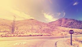 Винтажные стилизованные перекрестные дороги с знаком стопа Стоковая Фотография