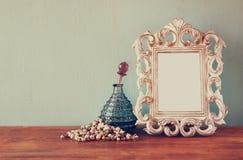 Винтажные флаконы духов antigue с старой картинной рамкой, на деревянном столе ретро фильтрованное изображение Стоковое Фото
