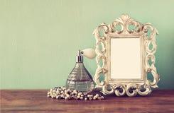 Винтажные флаконы духов antigue с старой картинной рамкой, на деревянном столе ретро фильтрованное изображение Стоковые Фото