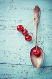 Винтажные ягоды ложки и вишни на старой деревянной доске Стоковое Изображение