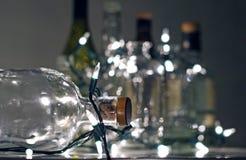 Винтажные ясные стеклянные бутылки ликера с светами рождества Стоковое Изображение RF