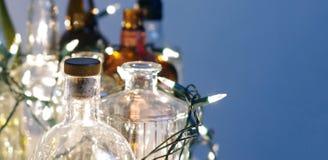 Винтажные ясные стеклянные бутылки ликера с светами рождества Стоковые Изображения RF