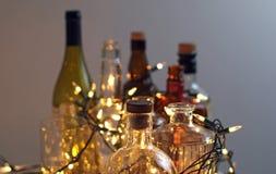 Винтажные ясные стеклянные бутылки ликера с светами рождества Стоковая Фотография RF