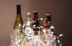 Винтажные ясные стеклянные бутылки ликера с светами рождества Стоковая Фотография