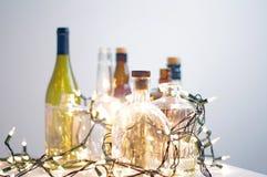 Винтажные ясные стеклянные бутылки ликера с светами рождества Стоковое Изображение