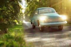 Винтажный автомобиль на солнечной дороге леса стоковое изображение