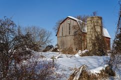 Винтажный амбар в поле снега стоковое изображение