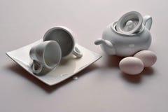 Винтажный белый чайник с крышкой опрокинул 2 белых квадрата чашки и поддонника и 2 мягких розовых яичка цыпленка на белой предпос Стоковая Фотография