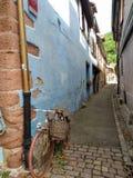 Винтажный велосипед полагаясь на голубой стене старого дома Kaysesberg стоковые фотографии rf