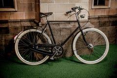 Винтажный велосипед припаркованный около дома стоковые изображения