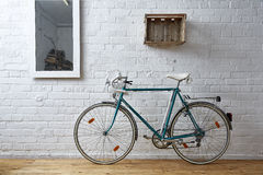 Винтажный велосипед в белой студии кирпича Стоковая Фотография RF